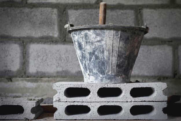 Tanque de cimento e colher em blocos de tijolos na área de construção