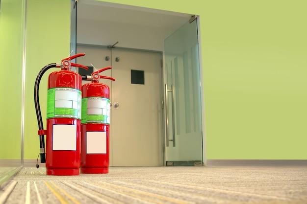Tanque de extintor de incêndio vermelho na porta de saída do prédio.