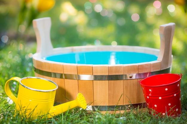 Tanque de madeira, regador e balde na grama verde no jardim de primavera
