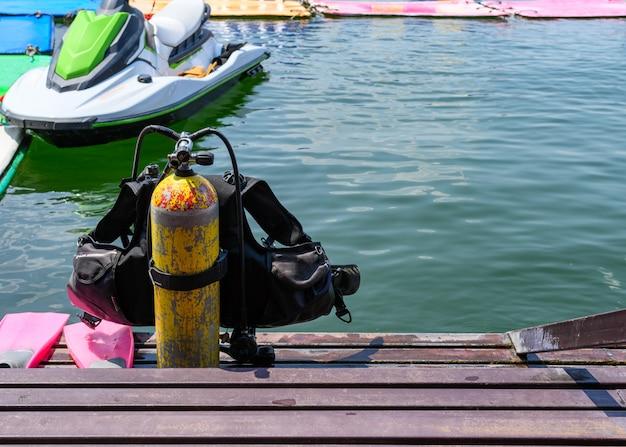 Tanque de oxigênio com colete salva-vidas e aletas em escadas de metal