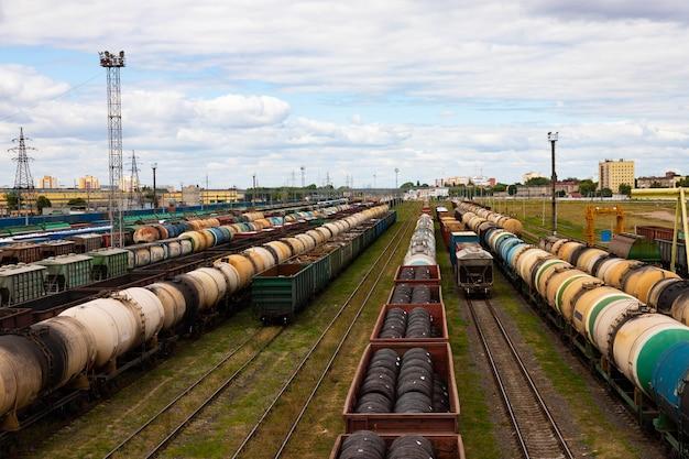 Tanques com combustível, vagões com carga em uma estação ferroviária de carga.