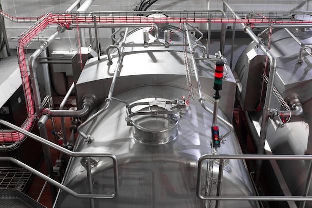 Tanques ou cubas de aço, tubulações e outras ferramentas de equipamentos na oficina da fábrica