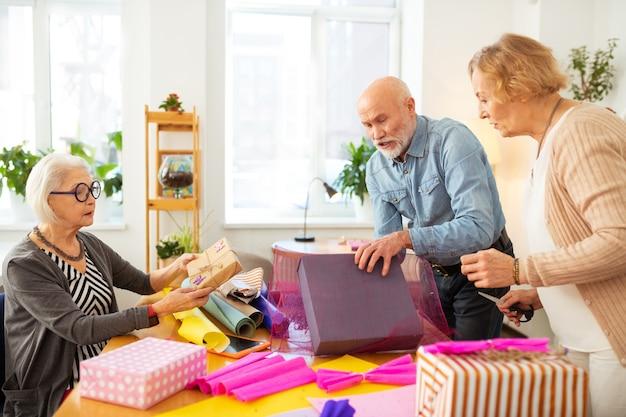 Tanto para fazer idosos amigáveis em pé ao redor da mesa enquanto se ocupam com a embalagem de presentes