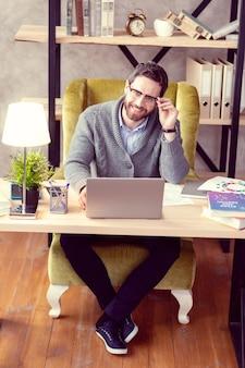 Tanto trabalho bom estressado homem segurando sua cabeça enquanto trabalhava em seu escritório