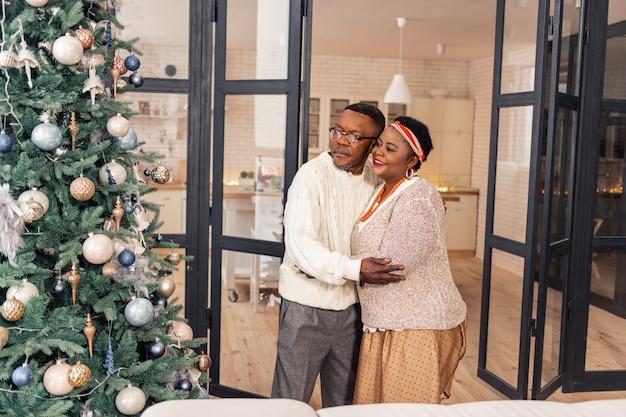 Tão bonito. casal africano alegre parado em frente à árvore de natal, olhando para ela