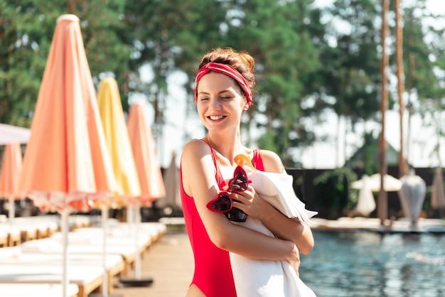 Tão brilhante. mulher feliz e simpática curtindo o sol enquanto está perto da piscina