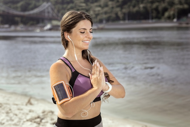 Tão conveniente. jovem simpática usando uma capa de telefone enquanto medita na praia