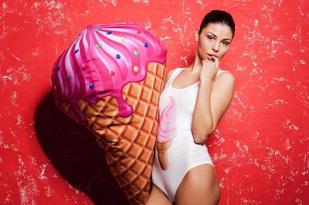 Tão doce! mulher jovem e bonita com roupas descoladas segurando um enorme sorvete falso em pé contra um fundo vermelho
