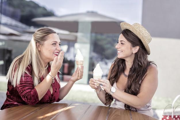 Tão doce. mulheres positivas e felizes tomando seu sorvete enquanto estão sentadas no café