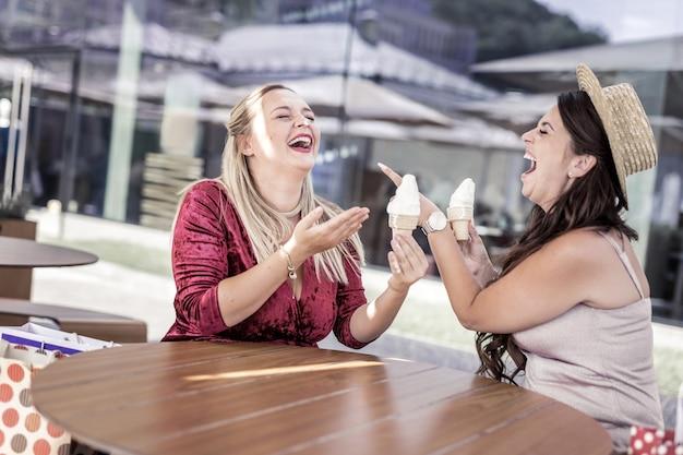 Tão engraçado. mulher alegre e feliz apontando para a amiga enquanto toma sorvete