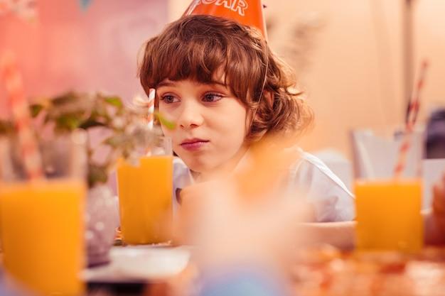 Tão entediado. criança atenta apertando os lábios enquanto olha para o copo com suco