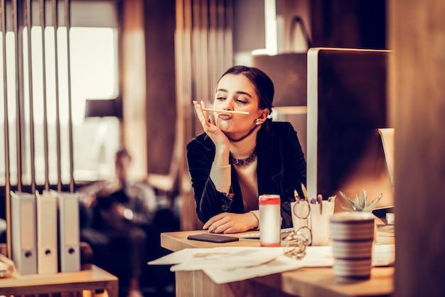 Tão entediado. mulher atraente sentada em seu local de trabalho e perdida em seus pensamentos