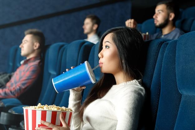 Tão entretido. retrato de uma jovem mulher asiática bebendo sua bebida assistindo filme atentamente no cinema local