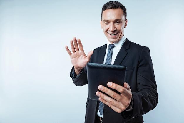 Tão feliz de vê-lo. cintura para cima foto de um homem alegre acenando para seu amigo enquanto segura um computador tablet e fala com ele durante uma videochamada em segundo plano.