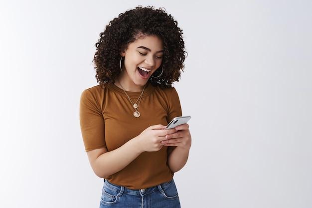 Tão incrível simples. alegre atraente jovem relaxado cabelo escuro encaracolado elegante garota rindo boca aberta animado lendo mensagem ousada segurar smartphone reagindo divertido vídeo engraçado display visual online