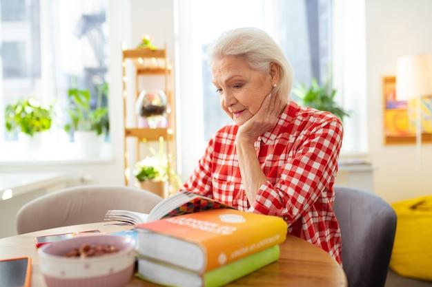 Tão interessante. agradável mulher idosa segurando a bochecha enquanto se dedica à leitura