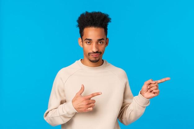 Tão manco, nossa. afro-americano homem bonito com bigode, sorriso de corte de cabelo afro cético olhando com expressão sarcástica, apontando bem insatisfeito e não impressionado, fundo azul