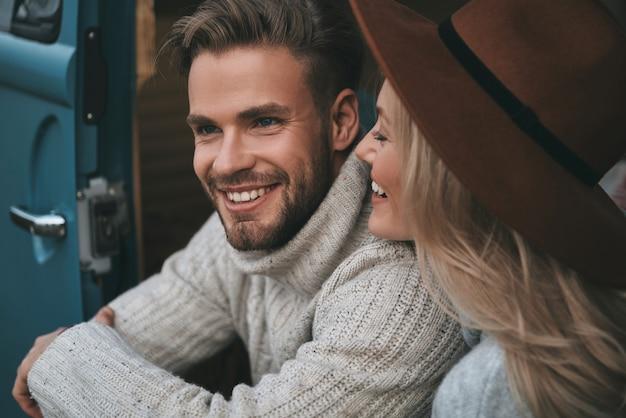 Tão perto. lindo casal jovem sorrindo enquanto está sentado em uma mini van azul estilo retro