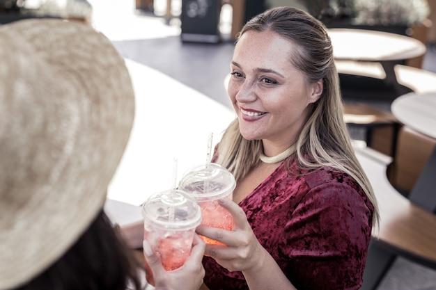 Tão saboroso. mulheres felizes e encantadas sorrindo uma para a outra enquanto bebem limonada juntas