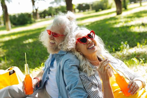 Tão sedento. casal feliz e alegre sorrindo enquanto bebe juntos