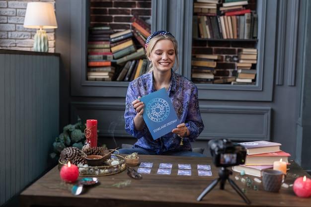 Tão útil. mulher alegre e atraente segurando seu livro favorito enquanto o mostra aos telespectadores