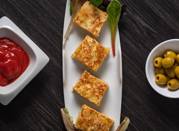 Tapa espanhola, omelete, azeitonas e molho