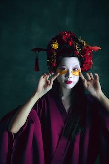 Tapa-olhos. jovem mulher japonesa como gueixa isolada em fundo verde escuro. estilo retro, comparação do conceito de eras. bela modelo feminina como personagem histórica brilhante, antiquada.