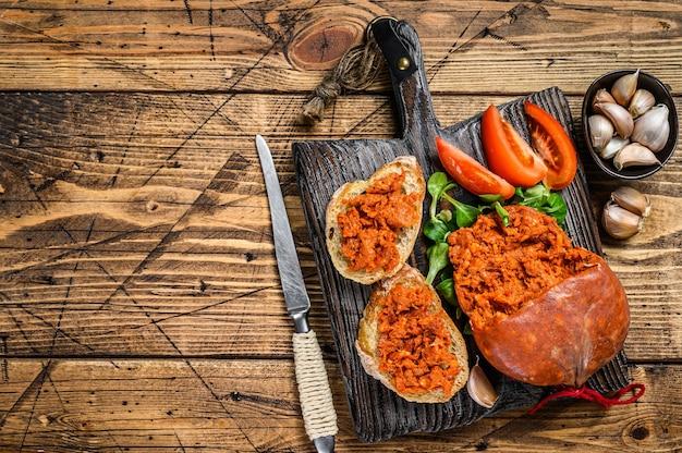 Tapaa com linguiça de porco curada sobrassada e tomate em tábua de madeira. fundo de madeira. vista do topo. copie o espaço.
