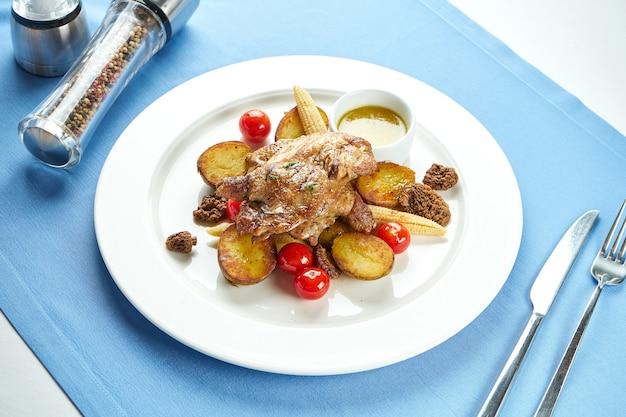 Tapaka de frango georgiano com batatas e vegetais grelhados em um prato branco sobre uma toalha de mesa azul. frango grelhado