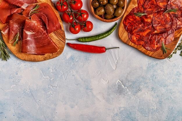 Tapas espanholas com chouriço, jamon, mesa de piquenique.