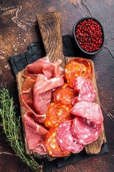 Tapas espanholas de carne - salame, jamon, salsichas curadas com choriso. fundo escuro. vista do topo.