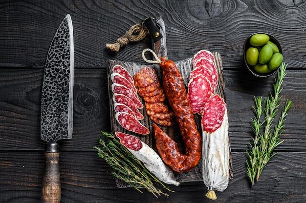 Tapas espanholas fatiadas de salame, fuet e chouriço em uma tábua de madeira
