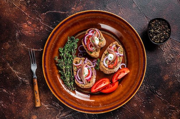 Tapas espanholas no pão com azeite, ervas, tomates e filetes de anchova picantes