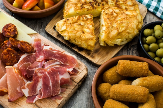 Tapas espanholas tradicionais. croquetes, azeitonas, omelete, presunto e patatas bravas na mesa de madeira