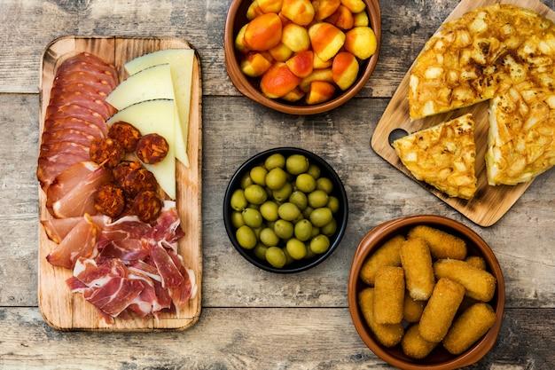 Tapas espanholas tradicionais croquetes, azeitonas, omelete, presunto e patatas bravas na mesa de madeira