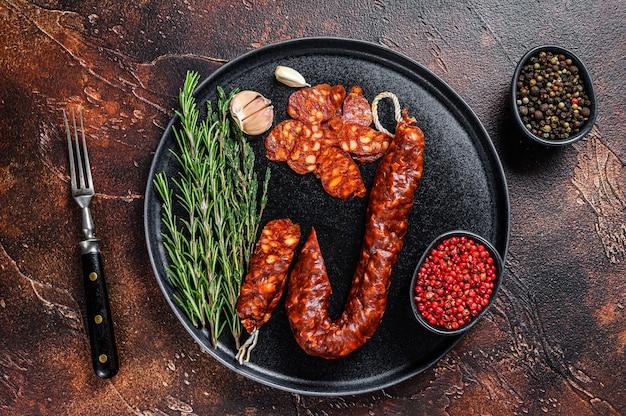 Tapas tradicionais espanholas salsicha curada de porco com chouriço fatiado. fundo escuro. vista do topo.