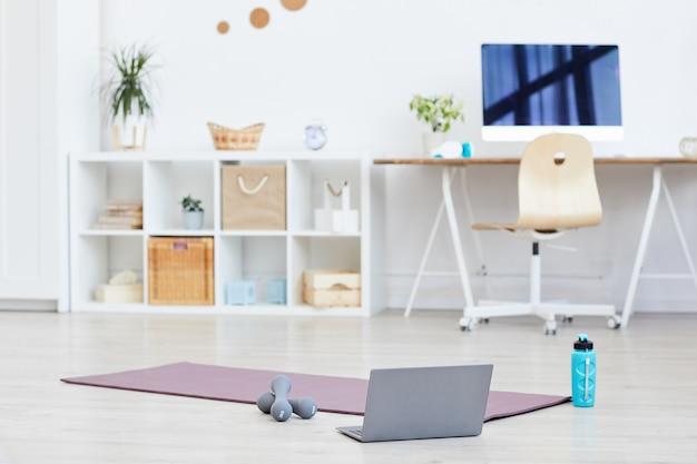 Tapete de exercícios com halteres e laptop no chão preparado para o treinamento esportivo em casa