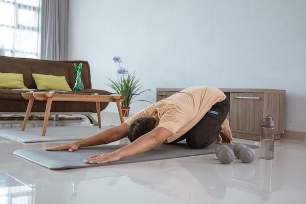 Tapete de exercícios de ajuste jovem asiático enquanto levanta uma perna e olhando para a direita.