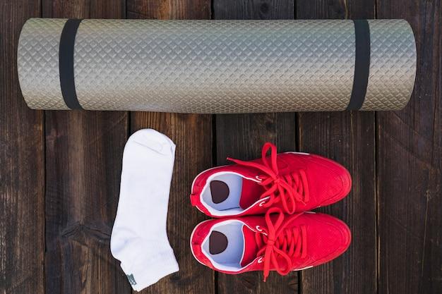Tapete de exercícios enrolado; meia e um par de sapatos de desporto vermelho na mesa de madeira