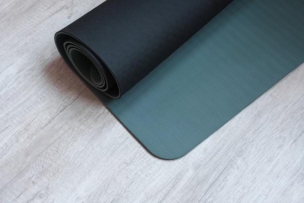 Tapete de exercícios no fundo de madeira clara para praticar ioga, fitness e outras atividades físicas. conceito de estilo de vida ativo e saudável