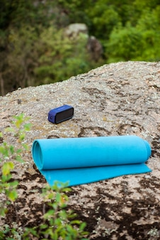 Tapete de ioga azul, alto-falante portátil sem fio na rocha no canyon