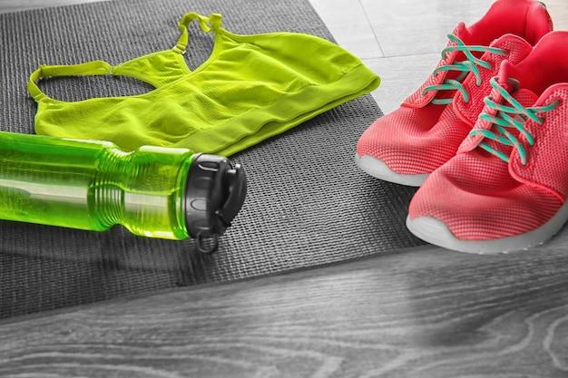 Tapete de ioga com garrafa de água, roupas esportivas e tênis em superfície de madeira