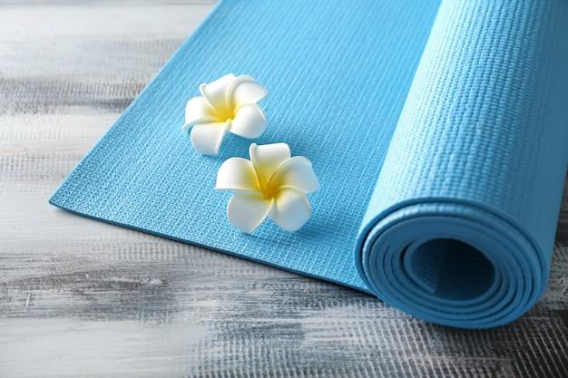 Tapete de ioga de cores e flores na mesa de madeira