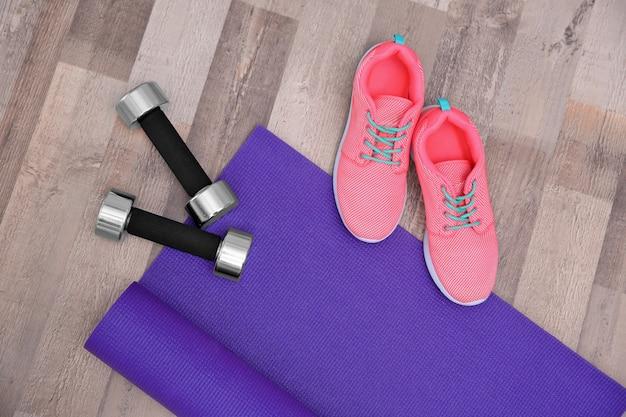 Tapete de ioga, tênis e halteres no chão de madeira