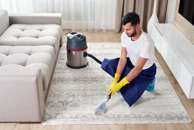 Tapete de limpeza de homem na sala de estar usando aspirador de pó em casa.