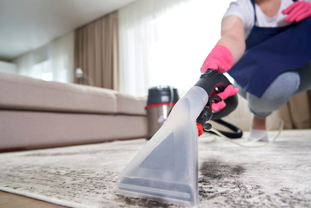 Tapete de limpeza humana na sala de estar usando aspirador de pó em casa