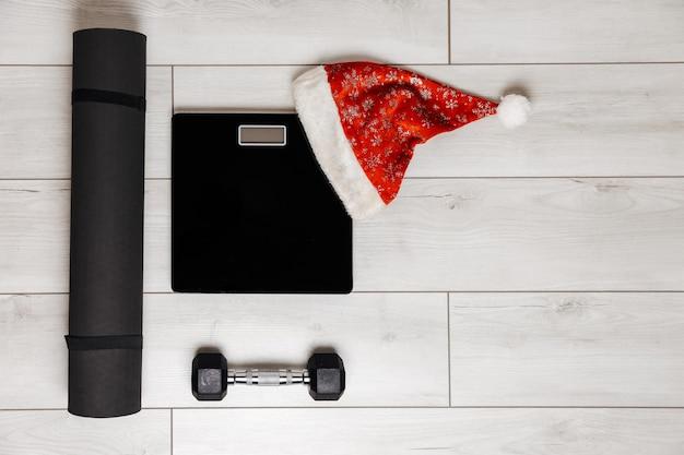 Tapete de pesagem preto e halteres em fundo cinza de madeira conceito de natal