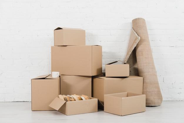 Tapete enrolado com pilhas de caixas de papelão no novo apartamento