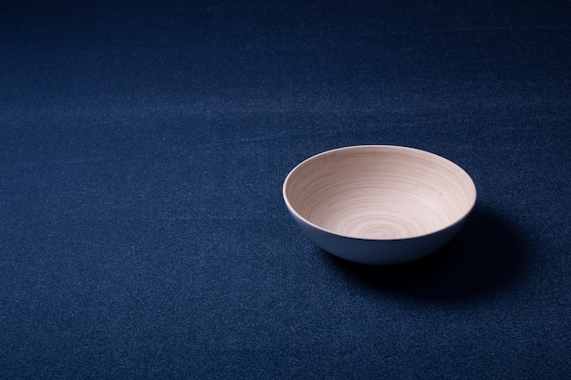 Tapete no chão do fundo. tapete de cor azul da mesma cor com uma tigela de madeira. design de interiores e produção.