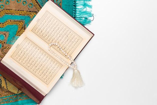 Tapete religioso com livro sagrado e pulseira